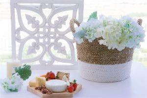 עציץ קלוע מקש עם פרחים לבנים, מגש חץ ועליו גבינות, אגוזים ותותים. שולחן ערוך לחג שבועות