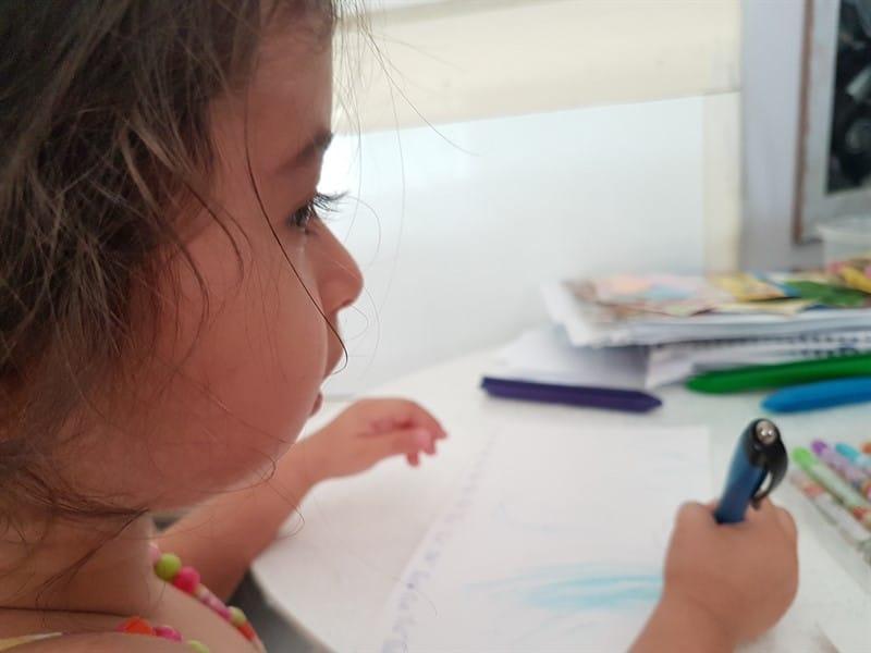 צילום של ילדה בפרופיל, מחזיקה עט. על השולחן לפניה טושים ונייר לציור.