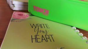 מחברת בצבע ירוק עם קלמר בצבע ירוק. על המחברת כתוב באנגלית כתוב את הלב שלך או כתבי את הלב שלך.