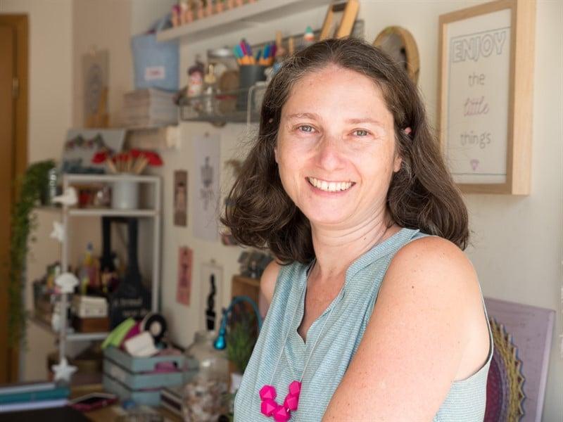 אשה מחייכת בחדר עבודה. חדר יצירה. עמנואלה בינר כותבת הספר פינה משלך.