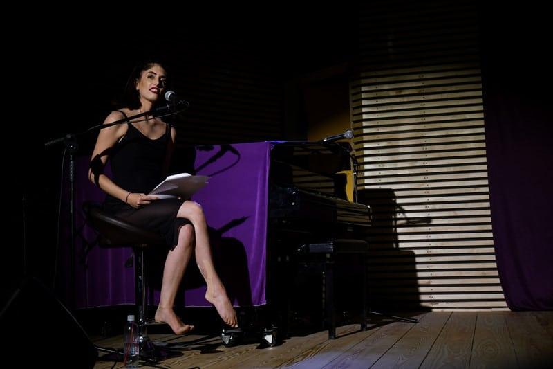 אישה בשמלה שחורה יושבת מול מקרופון ובידה גפים. יושבת יחפה על במה. עדי לשם.