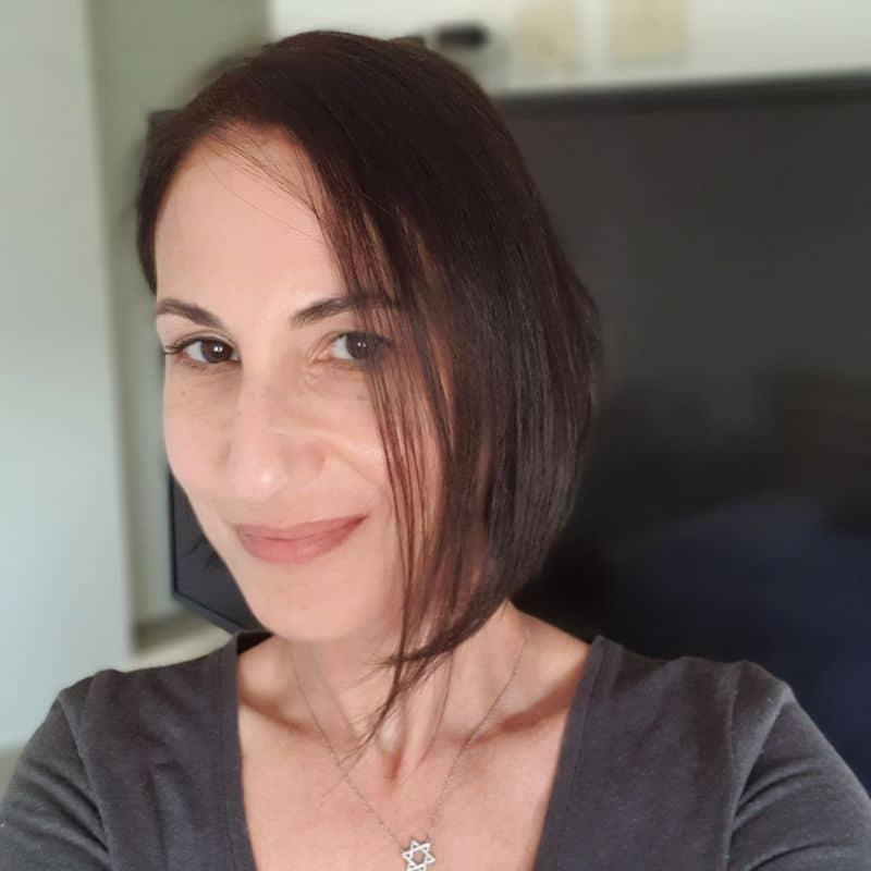 אישה מחייכת למצלמה עם תספורת קארה חדשה