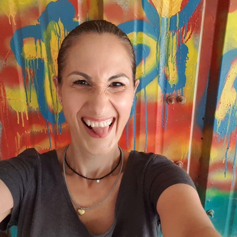 אישה מחייכת למצלמה עם לשון בחוץ וחצי קריצה. עומדת לפני קיר גרפיטי צבעוני. צילום סלפי של הצלמת לילך ברעם