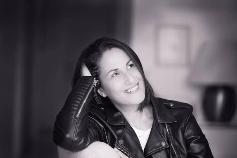 אישה מחייכת, הראש שעון על היד והיא מסתכלת הצידה