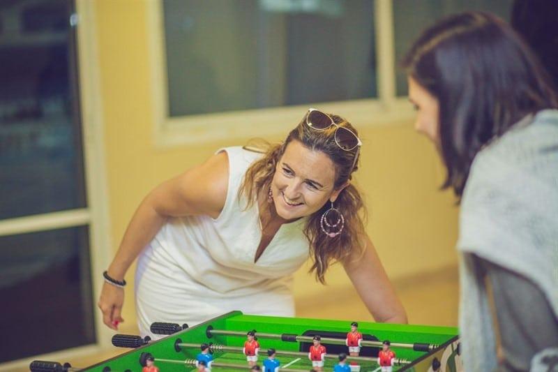 אישה לבושה שמלה לבנה, מתכופפת לשולחן כדורגל, מחייכת.