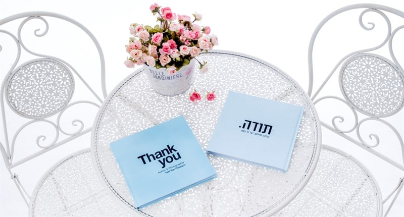ספר כחול שכתובה עליו בעברית ובאנגלית המילה תודה. על שולחן זכוכית עם אגרטל ופרחים ורודים