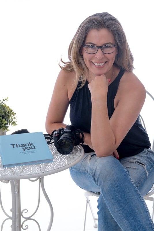 אשה יושבת שלובת רגליים על שולחן לידה מצלמה וספר תודה