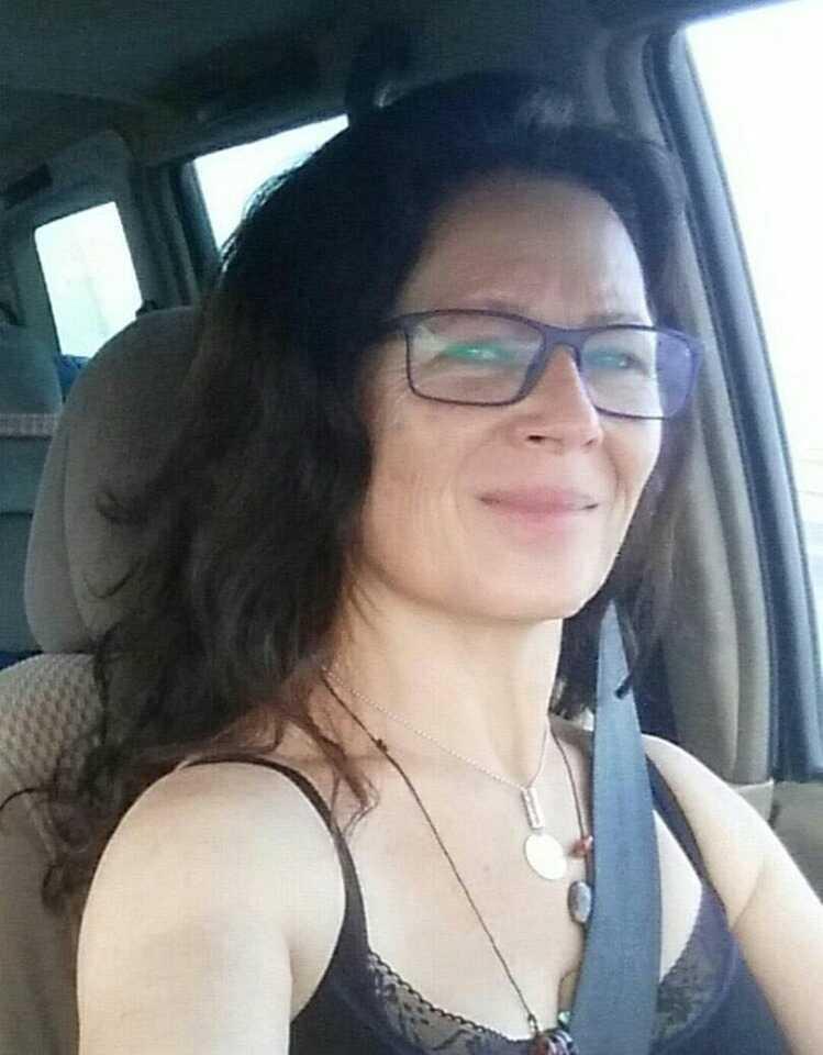 תמונת פורטרט של אישה ברכב, מחייכת