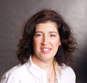 פורטרט אישה מחייכת למצלמה לבושה חולצה לבנה, מגריכת הורים וסופרת קרן עתי לוי