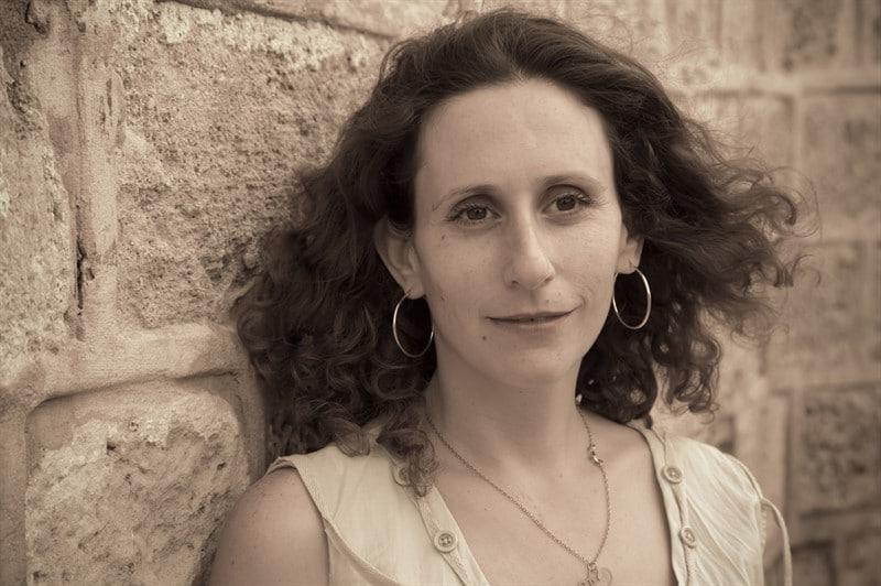 פורטרט אישה מחייכת חיוך קטן נשענת על קיר אבן ירושלמית. המשוררת יעל צבעוני