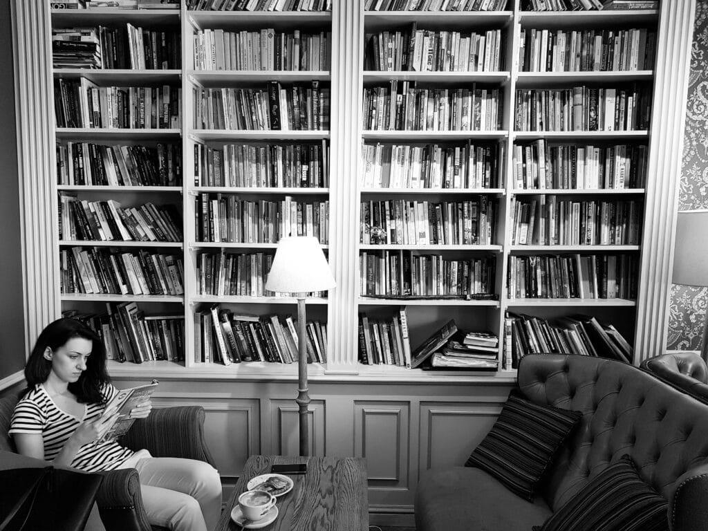 אשה יושבת על ספה וקוראת ספר. מאחוריה ספרייה גדולה מלאה בספרים. לפניה קפה ומאפה